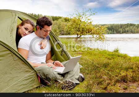 Remote Office stock photo, A couple looking at a computer while camping in a tent by Tyler Olson