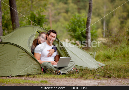 Computer Outdoor Tent stock photo, A man and woman using a computer outdoors in a tent by Tyler Olson
