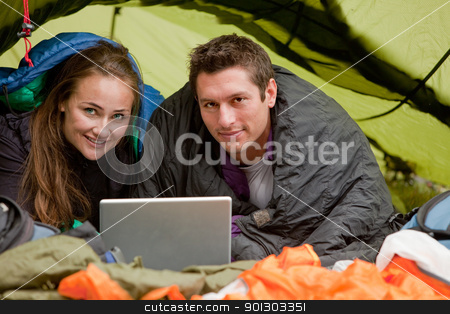 Camping with Computer stock photo, A happy couple in a tent using a computer looking at the camera by Tyler Olson