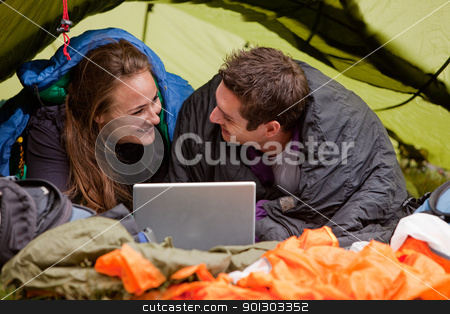 Camping with Computer stock photo, A happy couple in a tent using a computer looking at each other by Tyler Olson