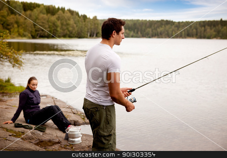 Fishing stock photo, A man fishing on a lake with camping equipment and woman in background by Tyler Olson