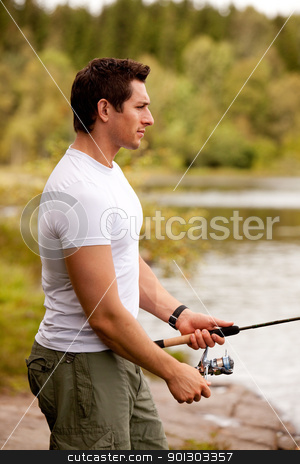 Fishing Portrait stock photo, A young adult fishing on an interior fresh water forest lake by Tyler Olson