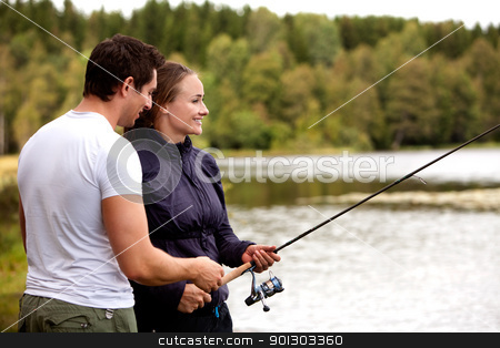 Man and Woman Fishing stock photo, A man showing a woman how to fish by Tyler Olson