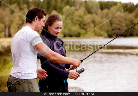 Teach Fishing stock photo, A man showing a woman how to fish by Tyler Olson
