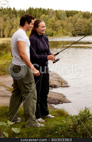 Fishing Fun stock photo, A young adult couple having fun fishing on a forest lake. by Tyler Olson