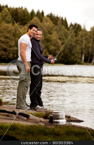 Woman Fishing stock photo, A man and woman fishing on a forest lake by Tyler Olson