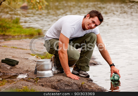 Fresh Water stock photo, A young male adult fetching fresh water from a forest lake by Tyler Olson