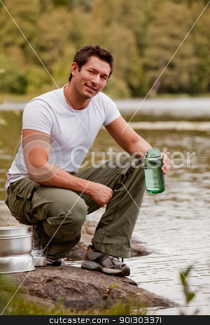 Camping Portrait Man stock photo, A man fetching water on a camping trip by Tyler Olson