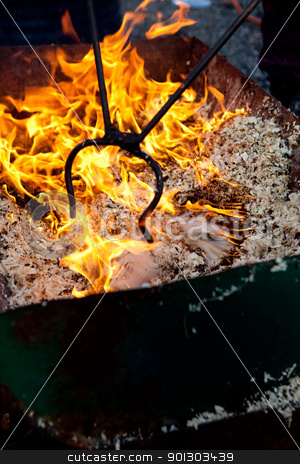 Raku stock photo, A raku burning pit filled with wood chips by Tyler Olson