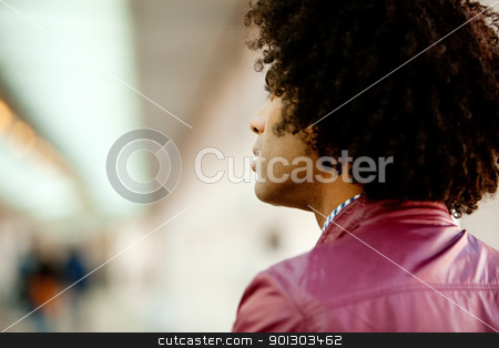 Wonder Question Man stock photo, An African American man with afro looking away from the camera by Tyler Olson