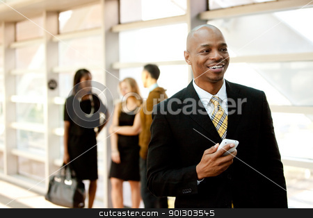 Business Man with Phone stock photo, A business man with a smart phone and co-workers in the background by Tyler Olson
