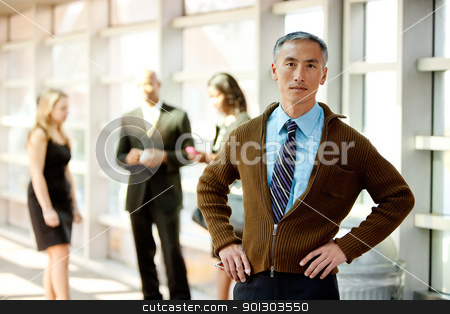 Casual Business Man stock photo, A cansual Asian looking business man with colleagues in the background by Tyler Olson