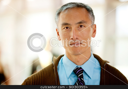 Casual Business Man stock photo, A portrait of a semi casual business man with colleagues in the background by Tyler Olson