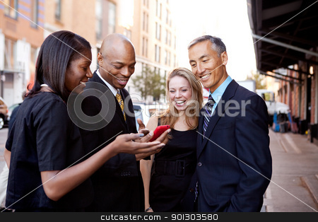 Show Phone Business stock photo, A group of business people looking at a cell phone and laughing by Tyler Olson