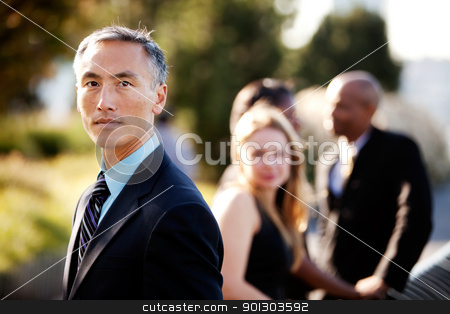 Serious Business Man stock photo, An Asian business man with a serious expression and colleagues in the background by Tyler Olson