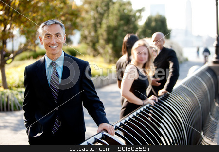 Asian Business Man stock photo, A group of business people outside - sharp focus on Asian man in foreground by Tyler Olson