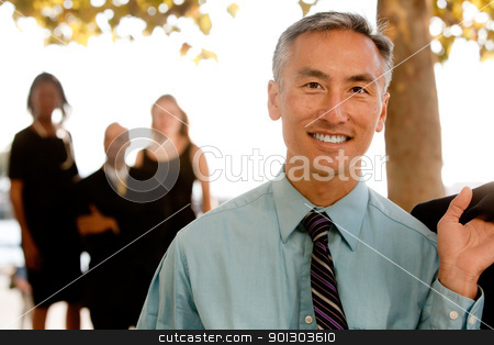 Asian Business Man stock photo, An asian looking business man with colleagues in the background by Tyler Olson