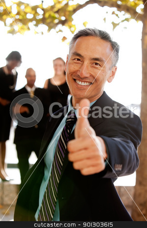 Thumbs Up stock photo, An asian looking business man with thumbs up - critical focus on eyes by Tyler Olson