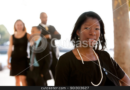 Attractive African American Business Woman stock photo, An attractive African American business woman with colleagues in the background by Tyler Olson