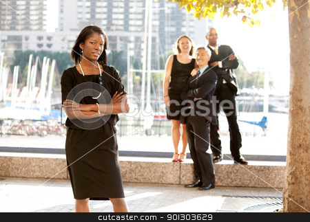 Business Team Woman stock photo, An African American woman in front of a business team by Tyler Olson