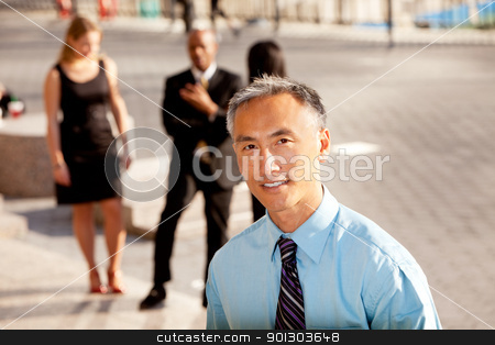 Business man stock photo, A casual business man with colleagues in the background - outdoor portrait by Tyler Olson
