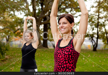 Stretching Exercise stock photo, Two women stretching in a park - outdoor exercise by Tyler Olson