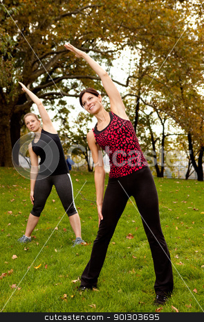 Stretch Park stock photo, A group of people stretching in a park - focus on front woman by Tyler Olson