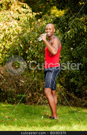 Fitness Man stock photo, A man exercising in the park, taking a break by Tyler Olson