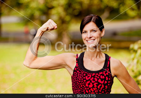 Fitness Woman stock photo, A pretty fitness model flexing her bicep by Tyler Olson
