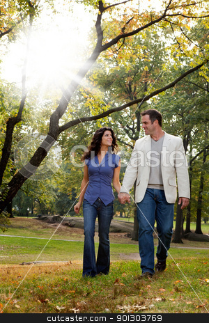 Park Couple Walk stock photo, A happy couple walking in the park - looking at each other by Tyler Olson