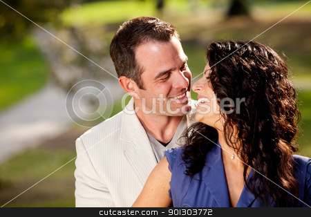 Happy Kiss Couple stock photo, A couple in the park happy and about to kiss by Tyler Olson