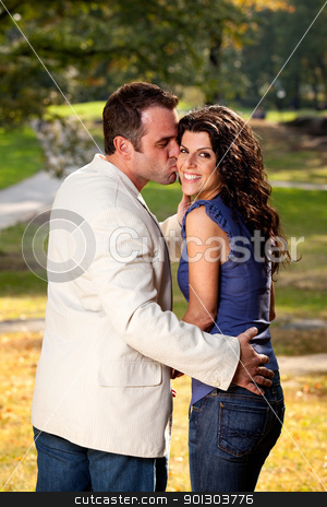 Couple Kiss Park stock photo, A couple kissing with the woman looking at the camera by Tyler Olson