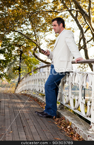 Cell Phone Man stock photo, A man checking his cell phone in a park by Tyler Olson