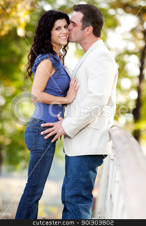 Kiss Man Woman stock photo, A man kissing a woman on the cheek in a park by Tyler Olson