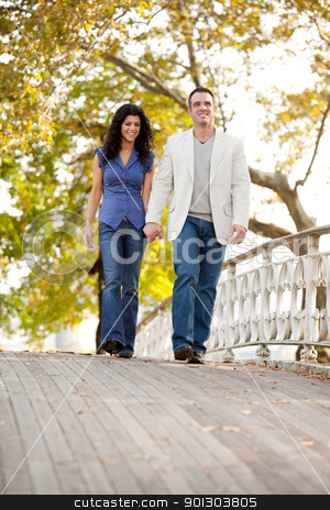 Couple Walk Bridge stock photo, A couple walking on a bridge in a park by Tyler Olson