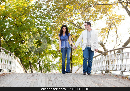Couple Walk Bridge stock photo, A couple walking on a bridge in a park by Tyler Olson