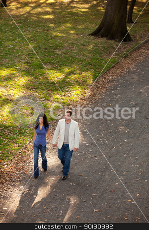 Park Walk Couple stock photo, A man and woman walking in a park on a sunny day by Tyler Olson