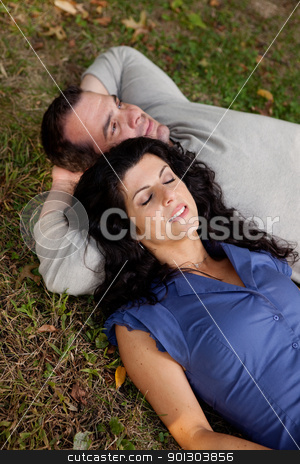 Man Woman Daydream stock photo, A couple laying on grass in a park daydreaming.  Focus on the womans eyes by Tyler Olson