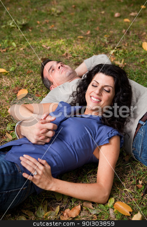 Couple Dream stock photo, A man and woman relaxing in the park laying in the grass and dreaming - focus on the woman by Tyler Olson