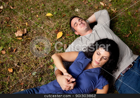Dream Couple Grass stock photo, A couple laying on grass dreaming - sharp focus on female by Tyler Olson