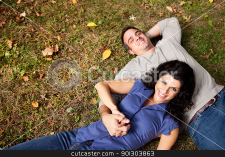 Daydream Park Couple stock photo, A happy couple daydreaming in a park on grass - sharp focus on woman by Tyler Olson