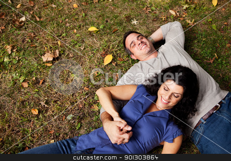 Daydream Park Couple stock photo, A happy couple daydreaming in a park on grass - sharp focus on man by Tyler Olson