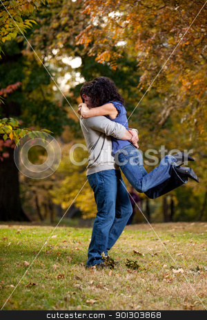 Big Hug stock photo, A man giving a woman a big hug - lifting her off the ground by Tyler Olson