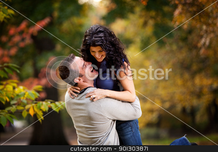 Excited Man and Woman stock photo, An excited couple giving eachother a big hug in a park by Tyler Olson