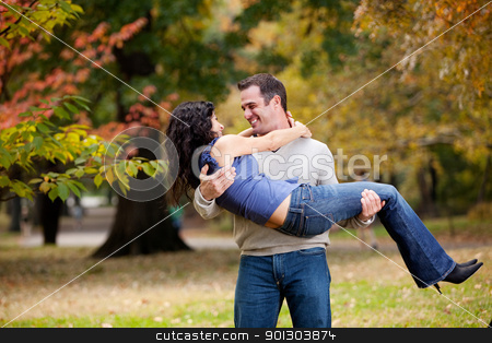 Man Holding Woman stock photo, A man holding a woman in a park - happy couple by Tyler Olson