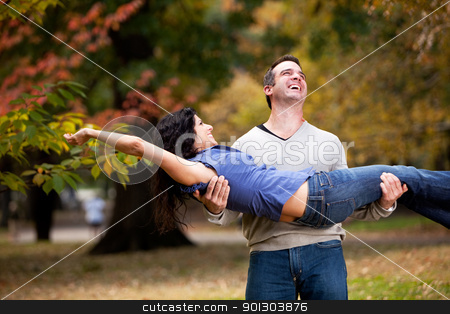 Playful Healthy Relationship stock photo, A playful couple - man holding woman in the park by Tyler Olson