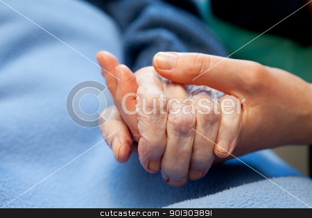 Old Hand Care Elderly stock photo, A young hand touches and holds an old wrinkled hand by Tyler Olson