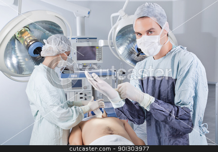Doctor getting ready for operation stock photo, Doctor getting ready before the operation in operating room by Tyler Olson