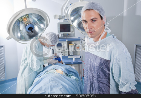 Male doctor confident while surgery stock photo, Confident male doctor in operating room by Tyler Olson
