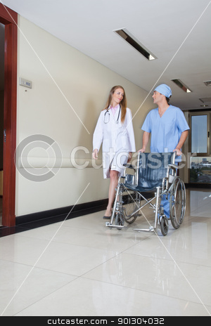 Doctor walking with male nurse stock photo, Doctor walking with male nurse pushing wheelchair by Tyler Olson